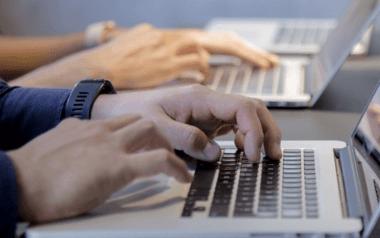 Des mains posées sur un clavier d'ordinateur